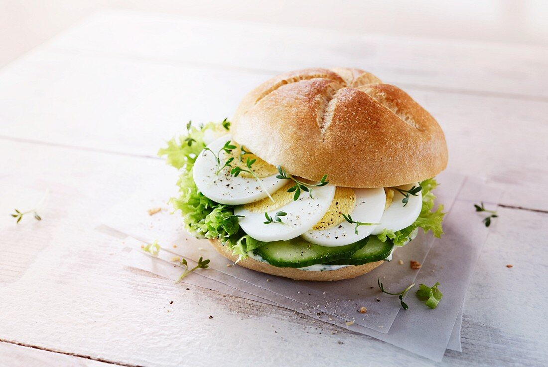 A roll with egg, cucumber, lettuce and cress