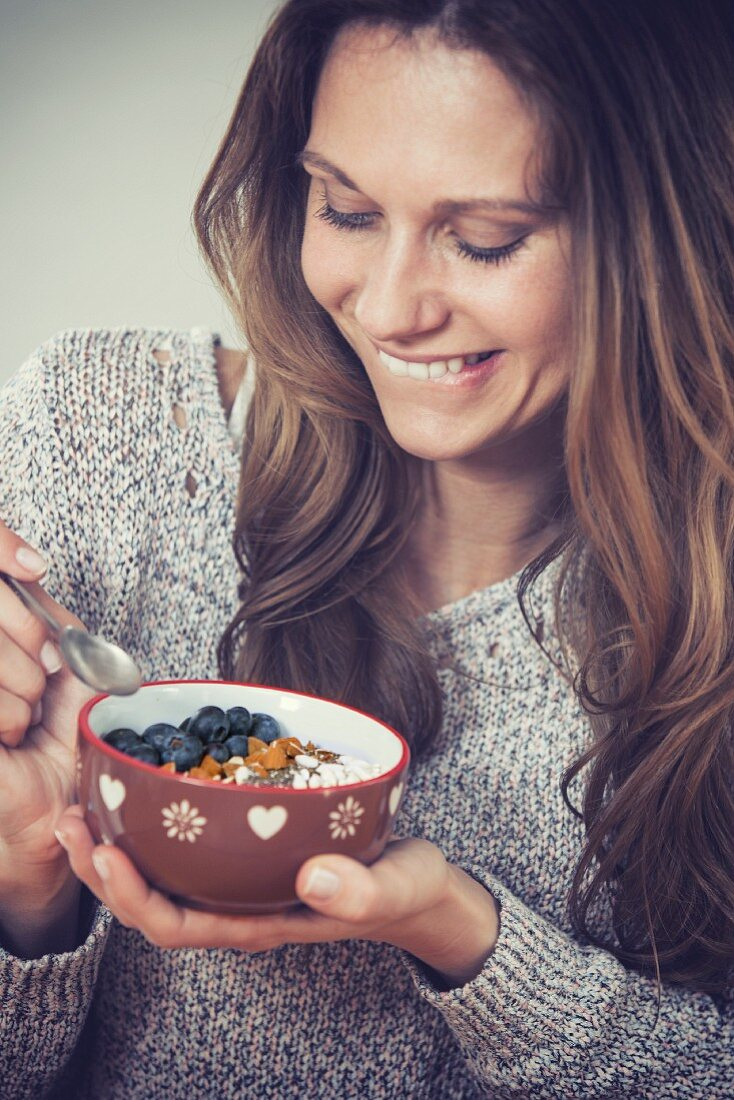 A young woman with a bowl of smoothie