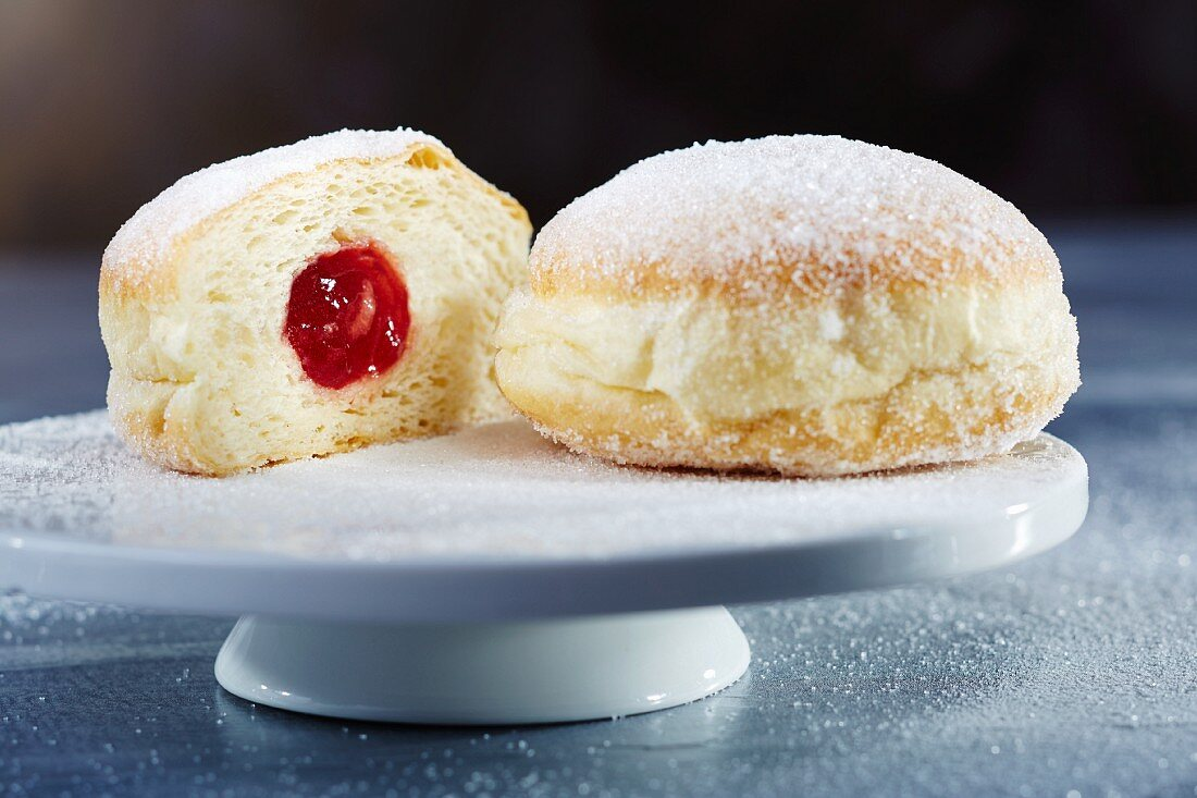 Doughnuts with icing sugar and jam, whole and halved