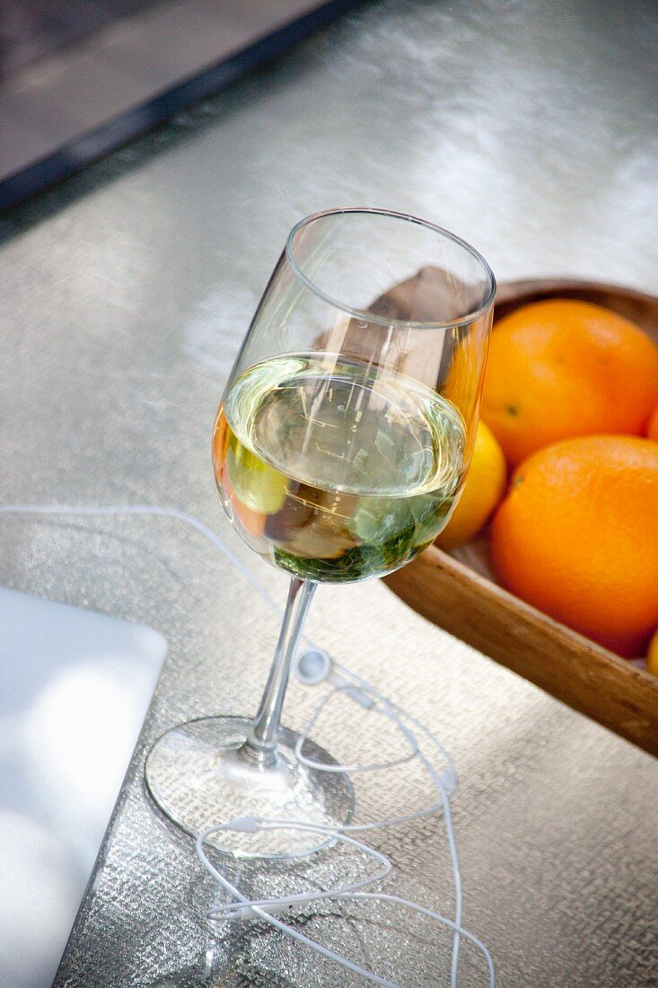 A glass of white wine, a laptop, headphones and citrus fruit
