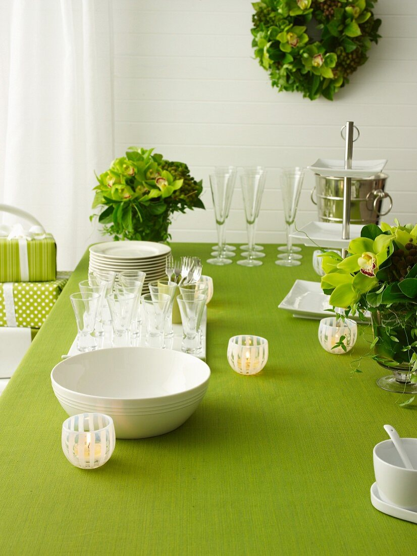 Stack of crockery, glasses and lanterns on green set table with flower decoration