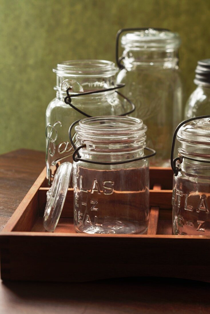 Several empty vintage flip-top preserving jars in a wooden crate