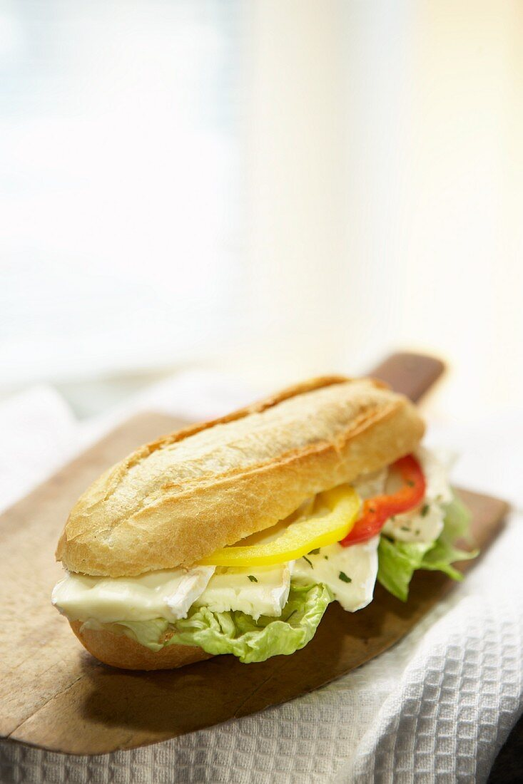 A baguette roll with brie and pepper