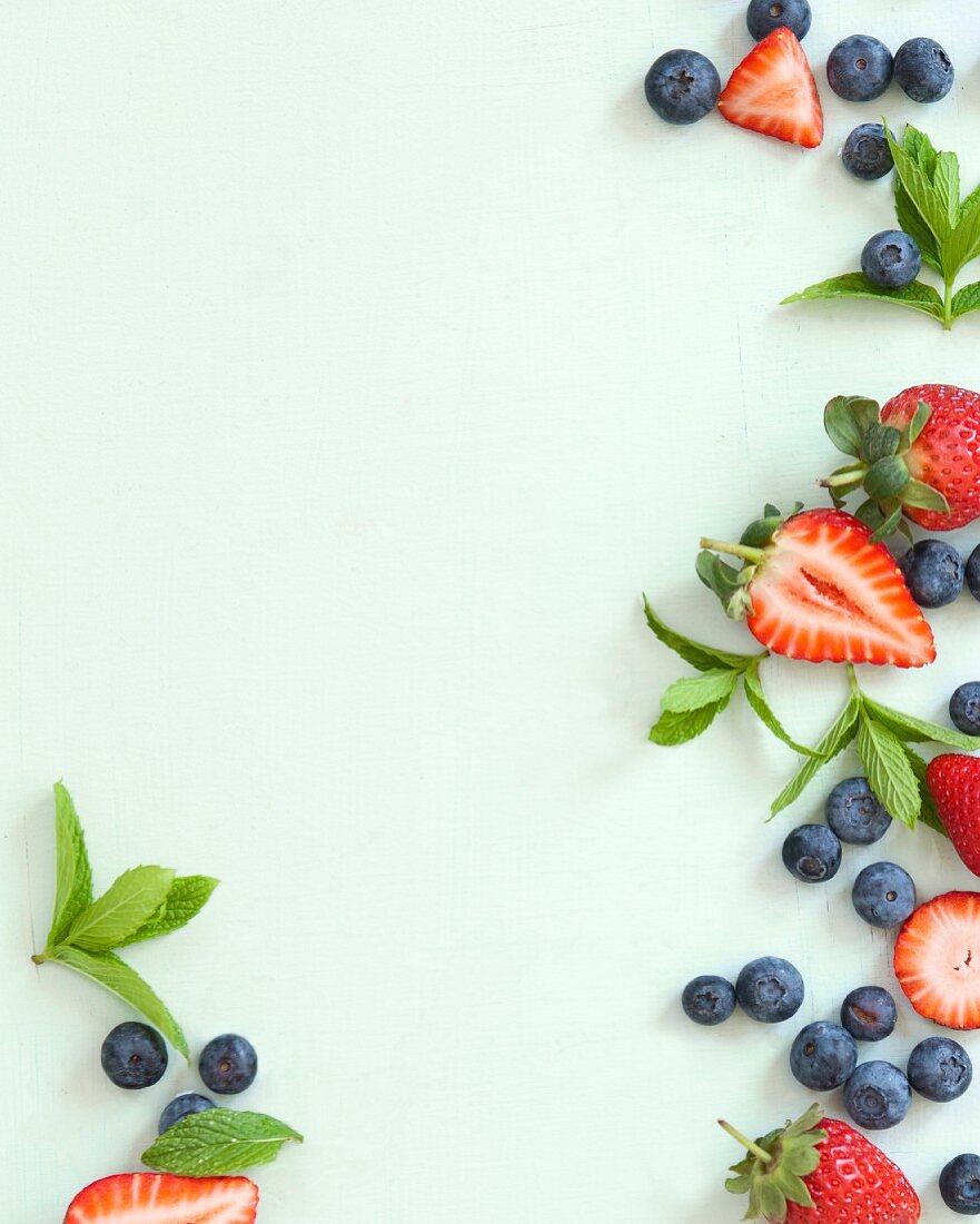 Frische Erdbeeren, Heidelbeeren und Minze am Bildrand
