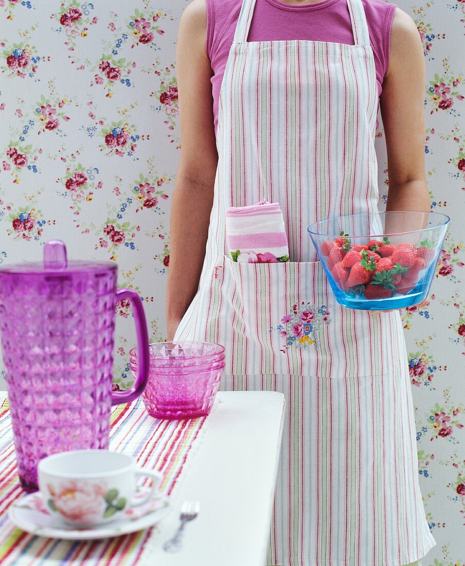 Woman wearing striped apron holding glass bowl of strawberries in front of romantic floral wallpaper