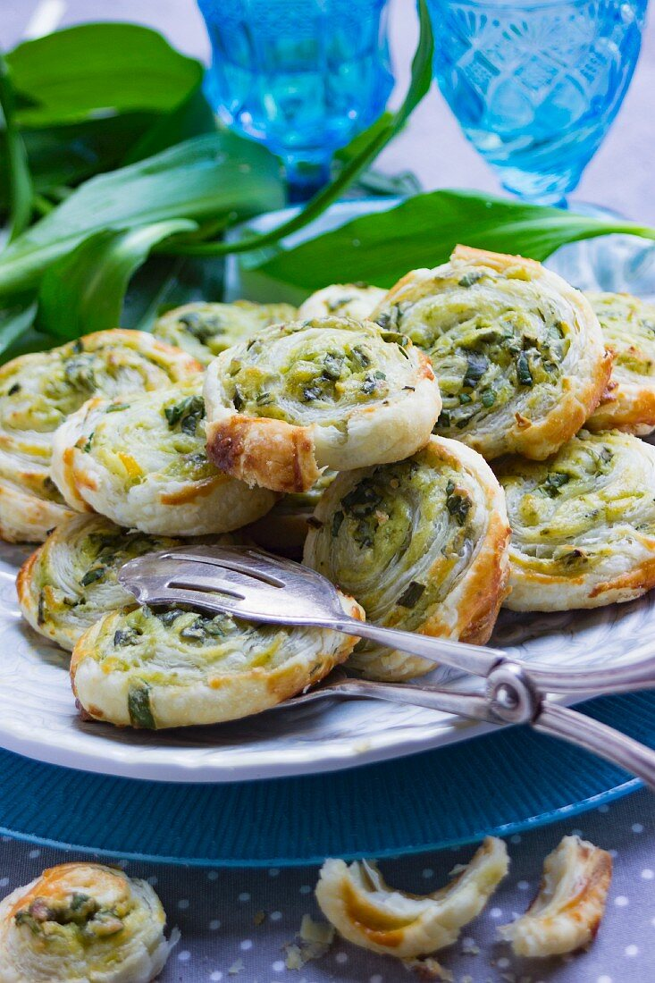 Vegetarian wild garlic pastries on a plate with a pair of pastry tongs and fresh wild garlic