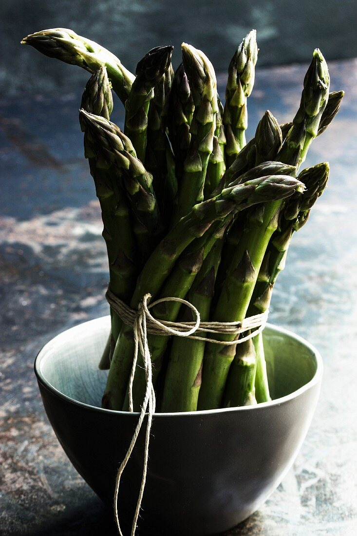 A bundle of green asparagus in a green bowl