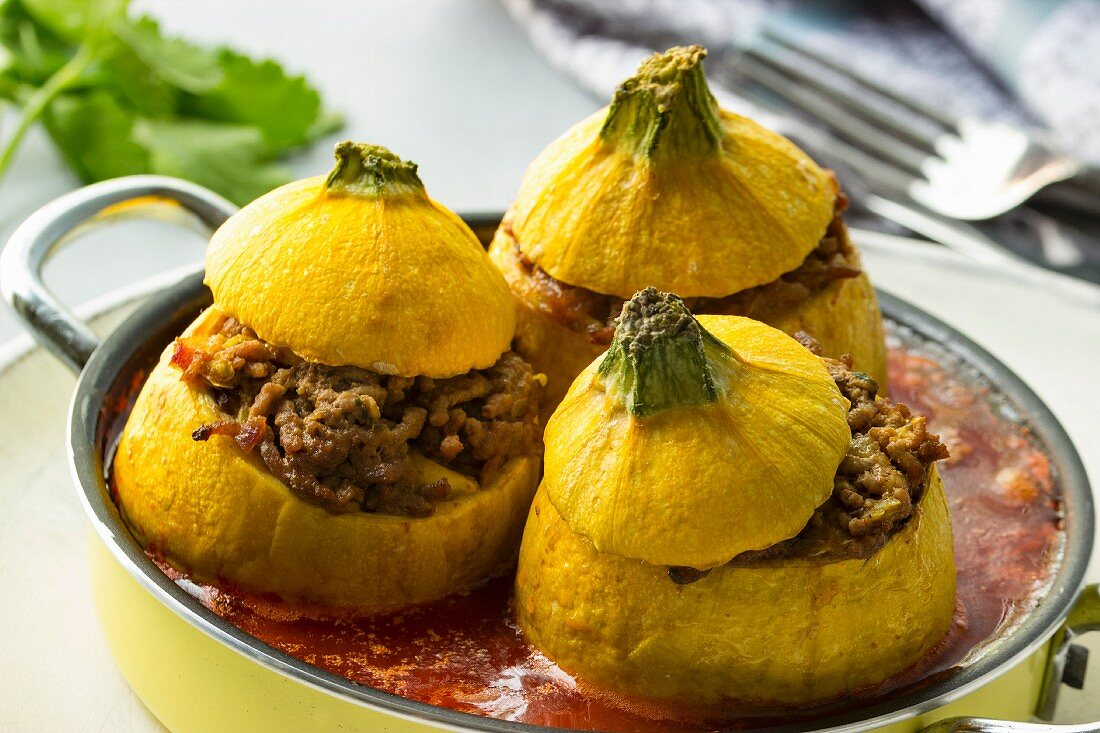 Yellow squash filled with minced meat and tomato sauce and cutlery