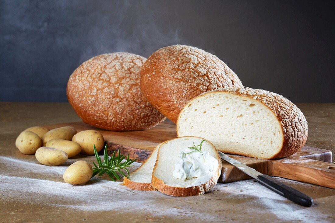 Three loaves of potato and wheat bread on an olive wood board with potatoes, rosemary and herb quark