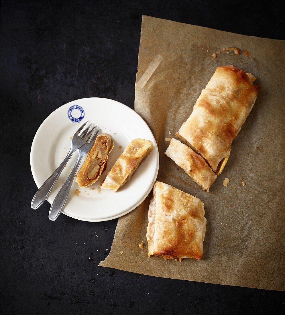 Apple strudel on baking paper and on a plate (seen from above)