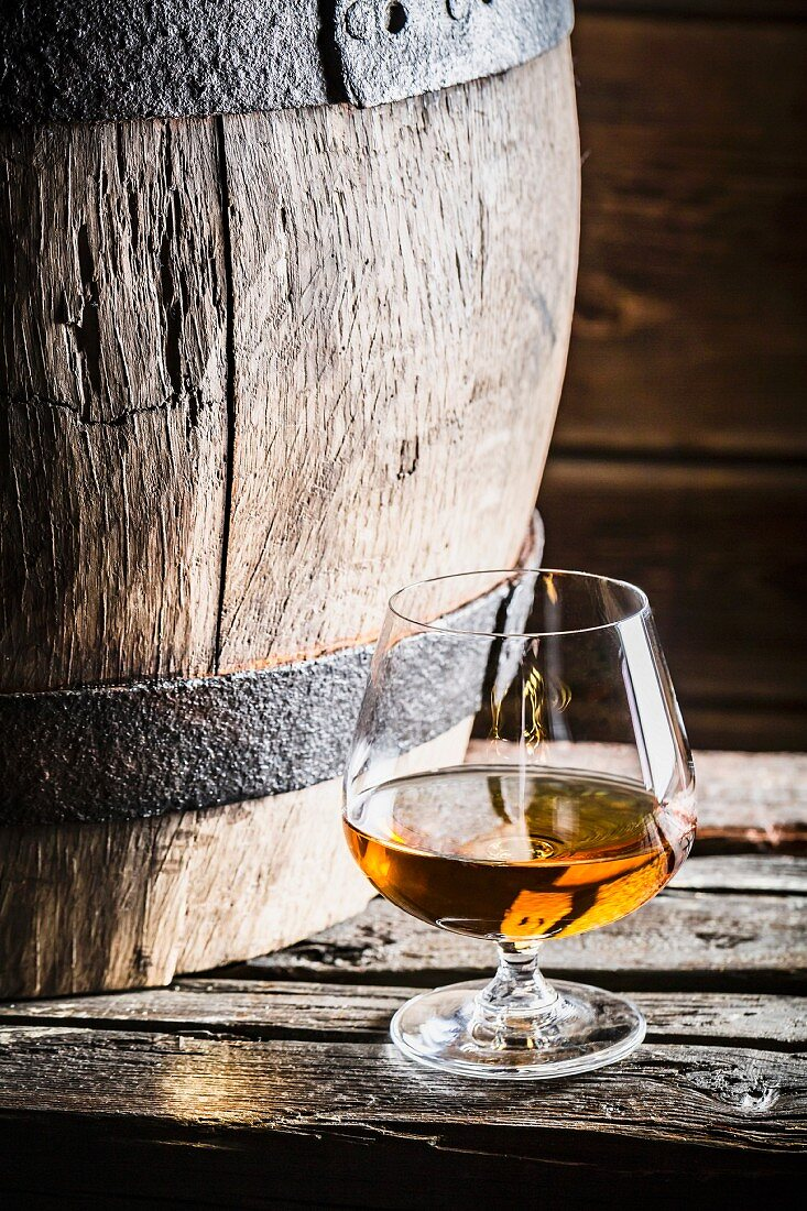 A glass of cognac next to an old wooden barrel