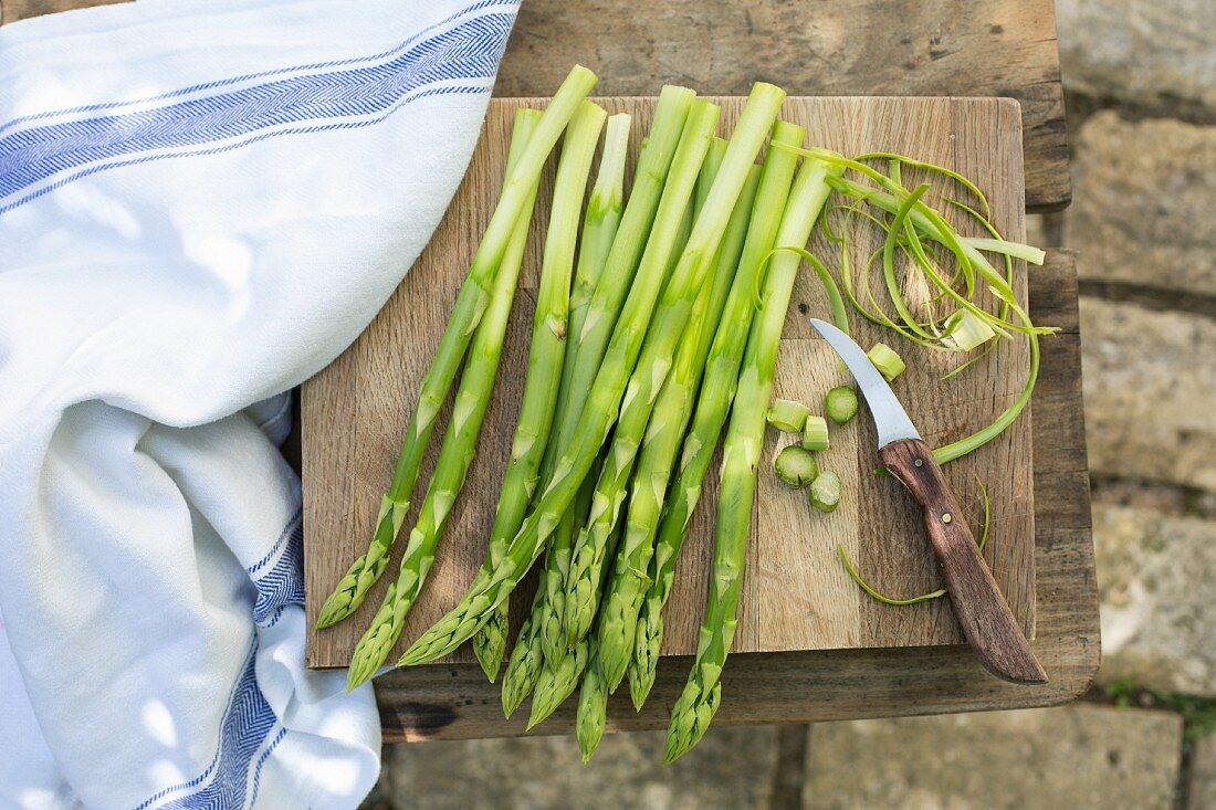 Green asparagus on a chopping board with a knife