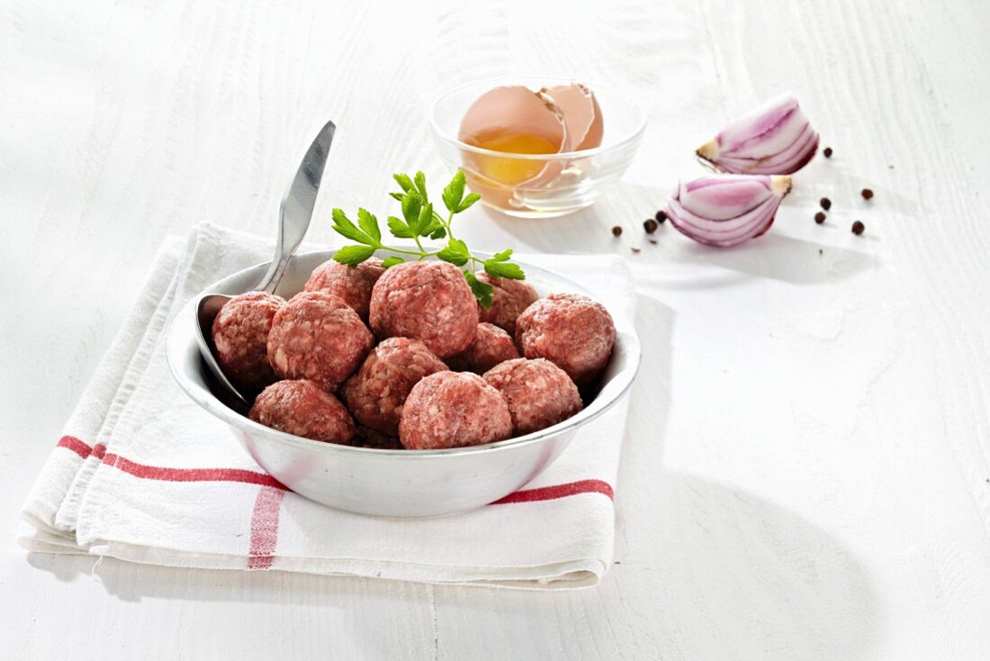 Raw meatballs, broken eggs, onions and spices
