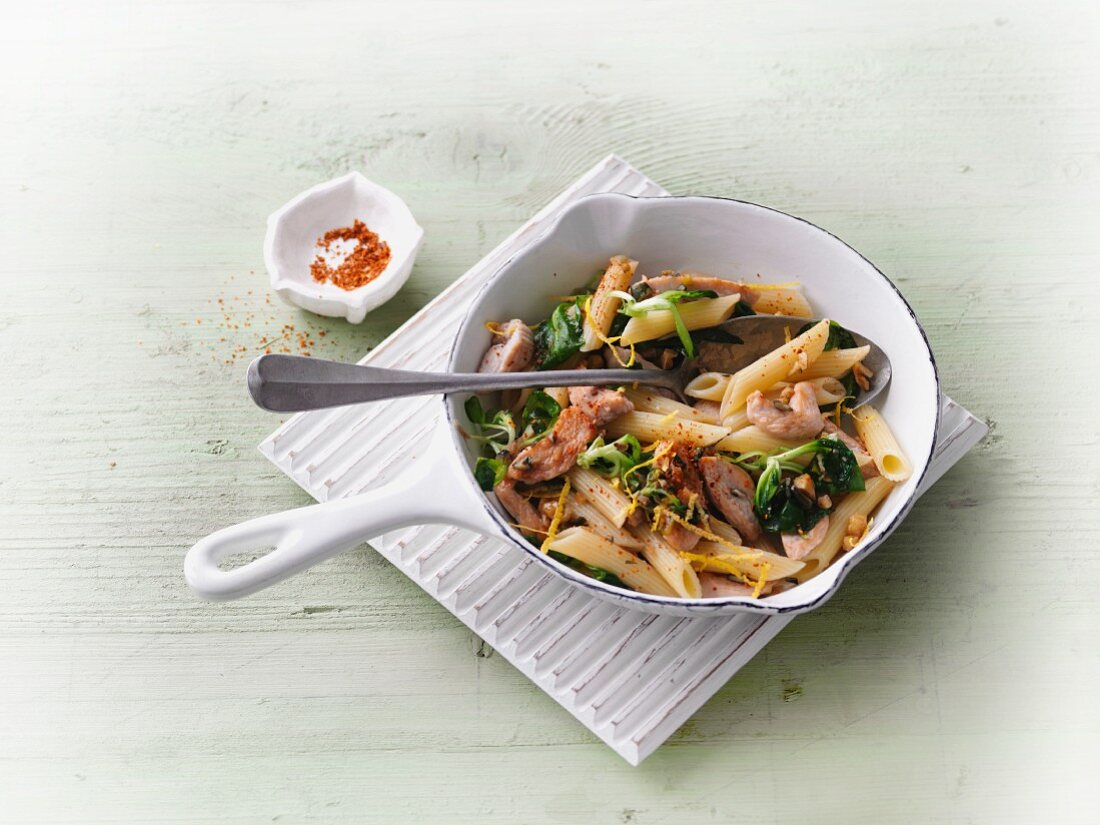 Penne pasta with turkey breast, lemon and nut sauce and lamb's lettuce
