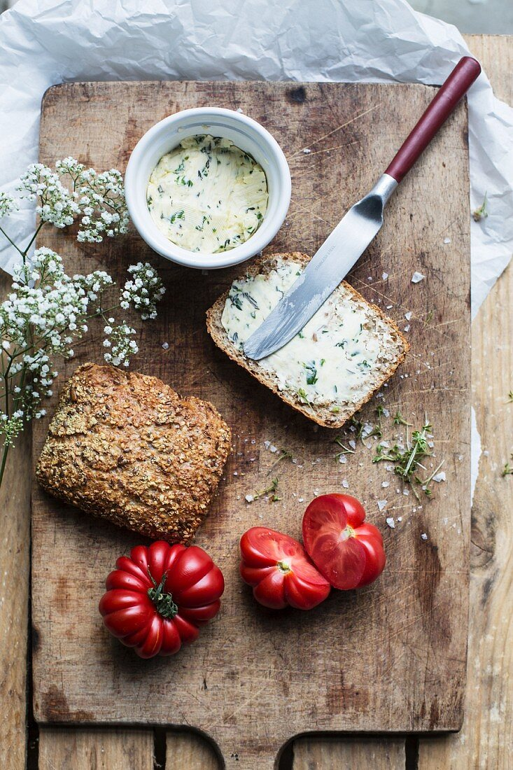 Bread with herb butter and tomatoes on an old chopping board