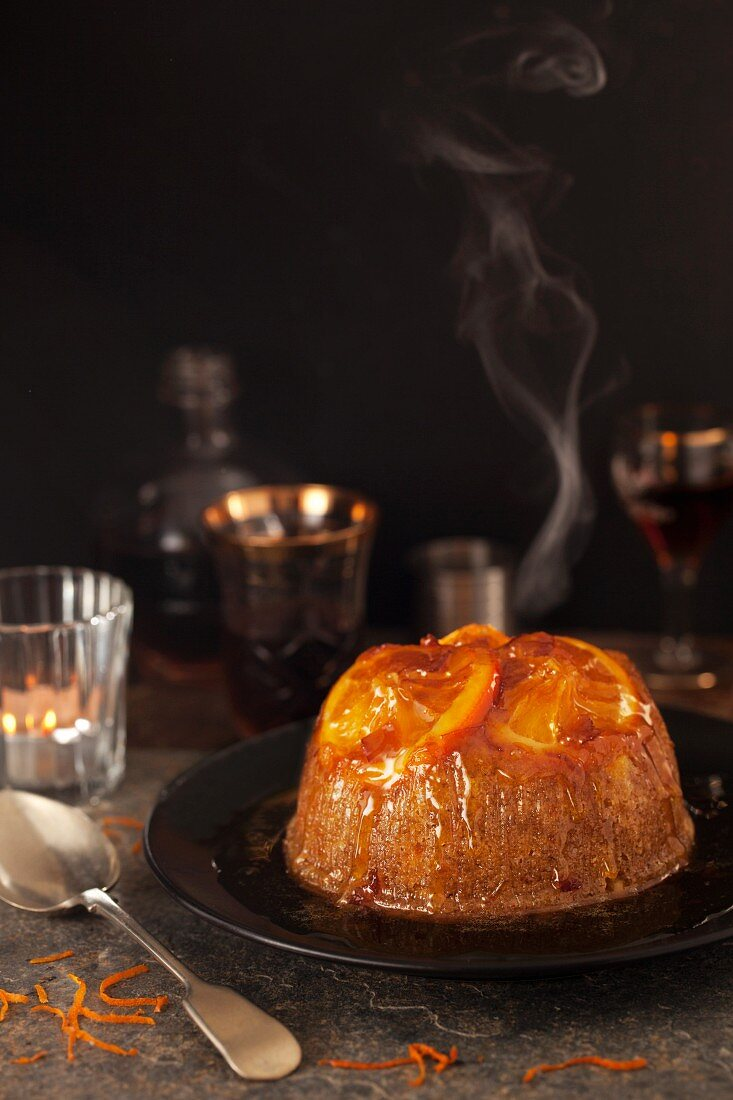 A steamed sponge pudding topped with orange slices and syrup (England)