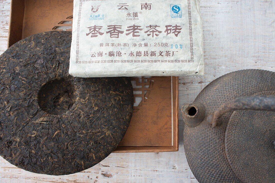 An arrangement featuring a teapot and a pu-ehr tea brick