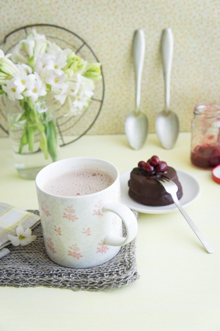 Hot chocolate with sugar beet syrup served with a mini chocolate cake