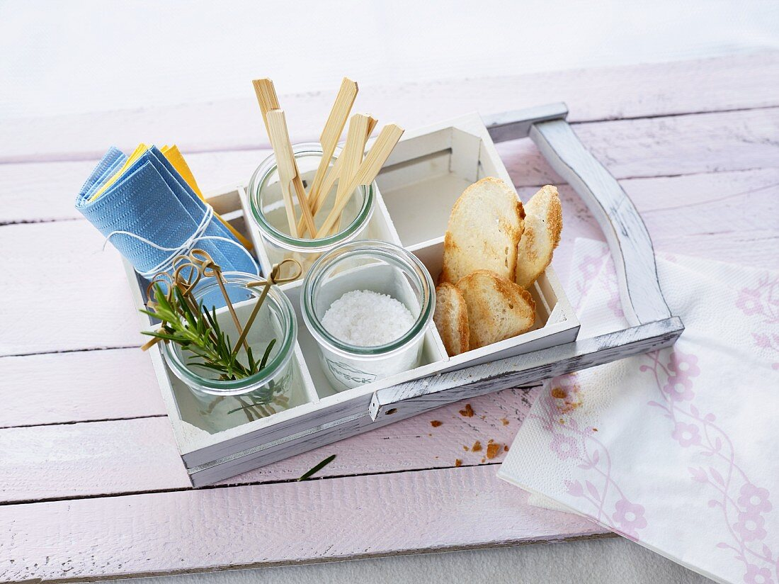 Grilled bread, salt, rosemary and wooden sticks on a wooden tray