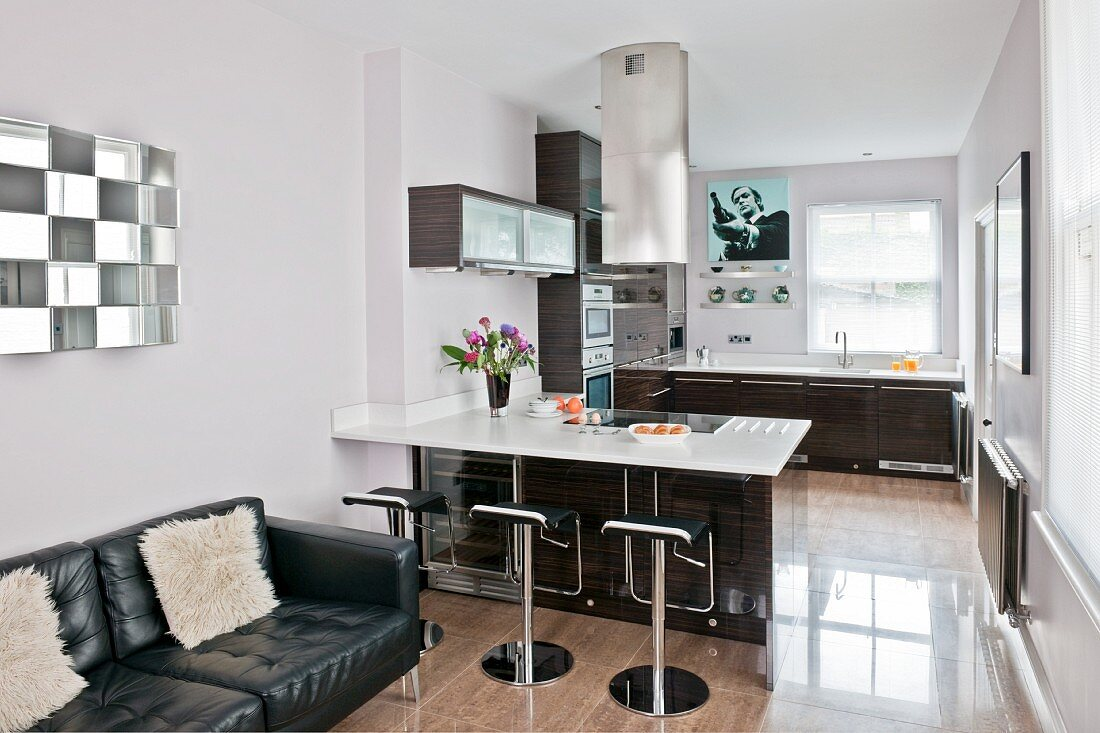 A leather sofa and a fitted kitchen with barstools at a counter; part of a long, open-plan living area with a polished, ceramic-tiled floor