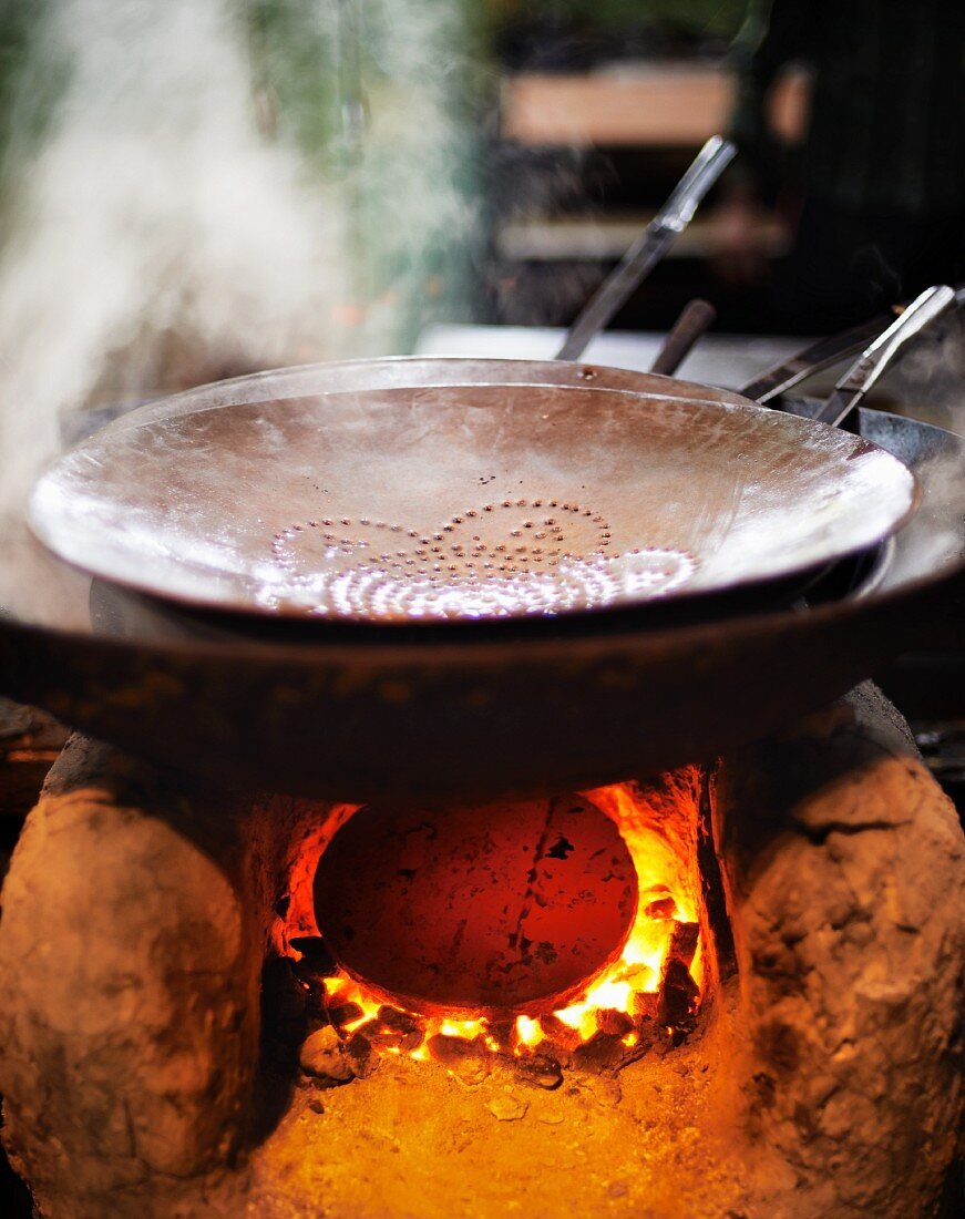 A steaming pan of oil on a traditional clay stove