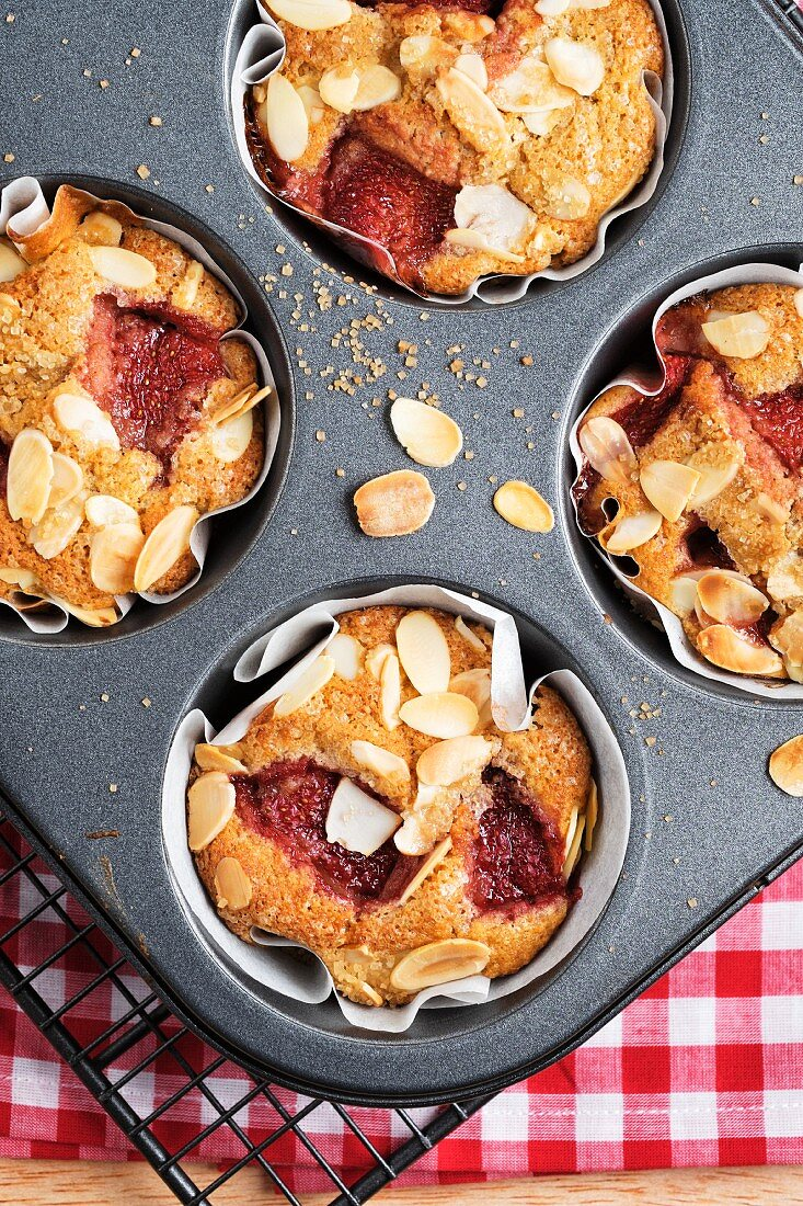 Strawberry muffins with apples and almonds in a muffin tin (seen from above)
