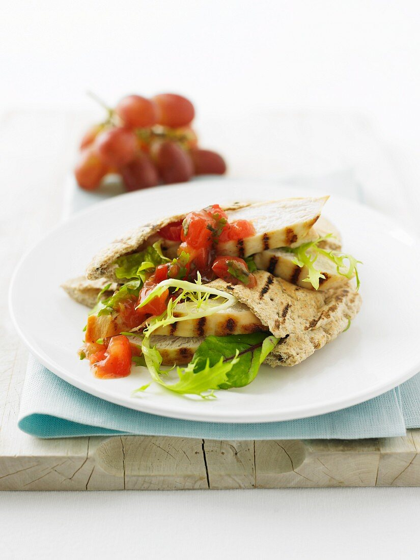 A pita bread filled with grilled chicken breast and tomato salsa