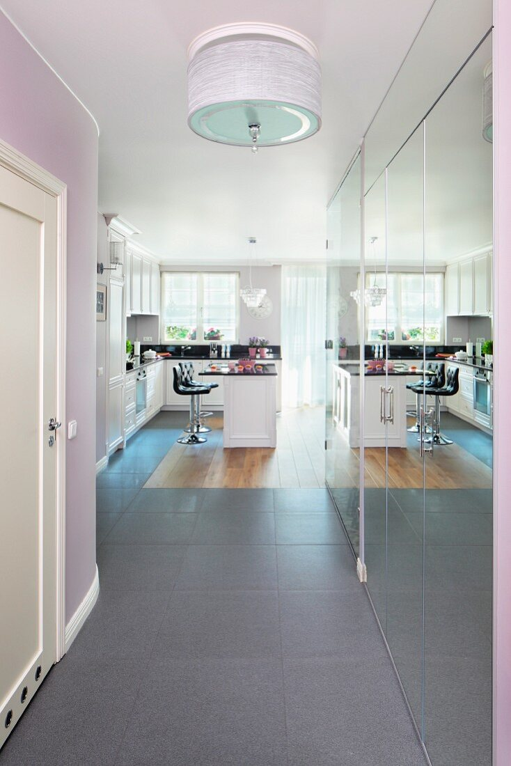 A view down a hallway with a built-in mirrored cupboard reflecting a breakfast bar in an open, black and white fitted kitchen