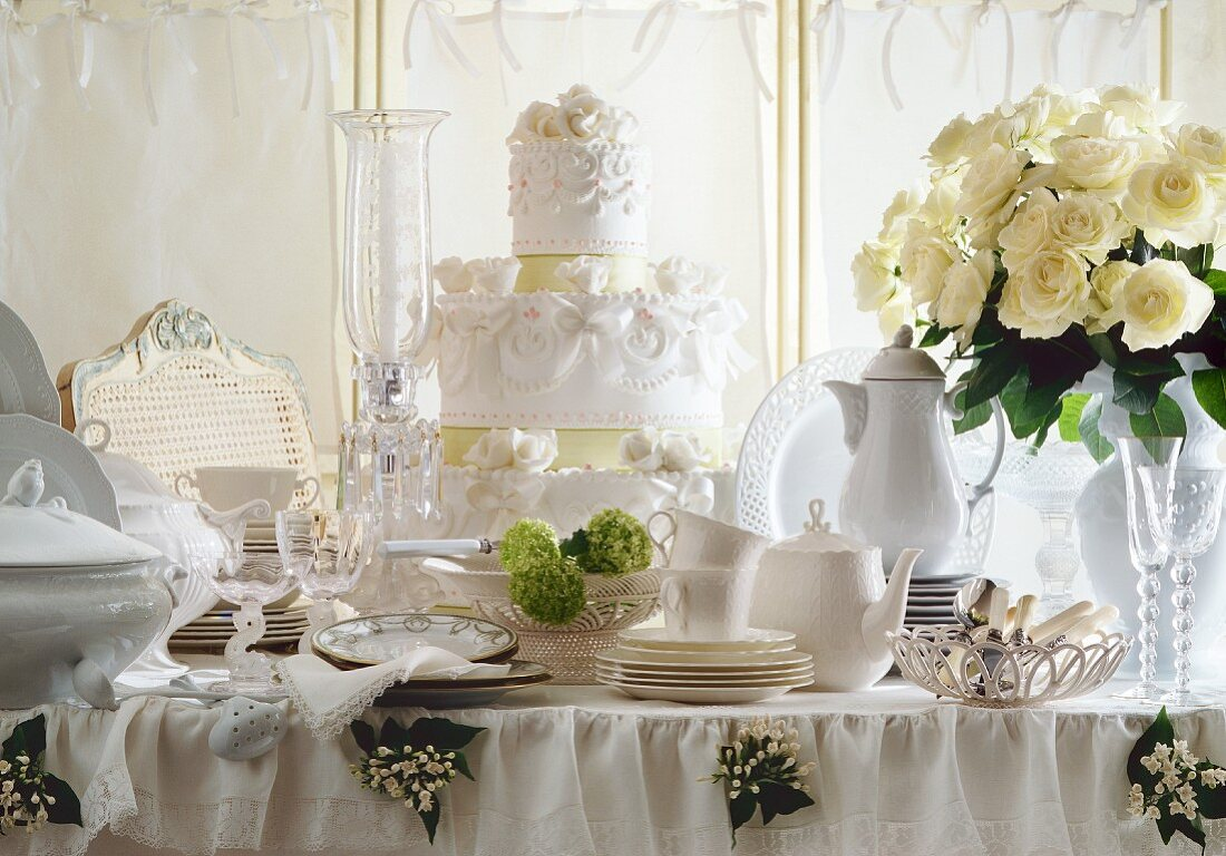 A bunch of white roses and artistically decorated wedding cake on a table