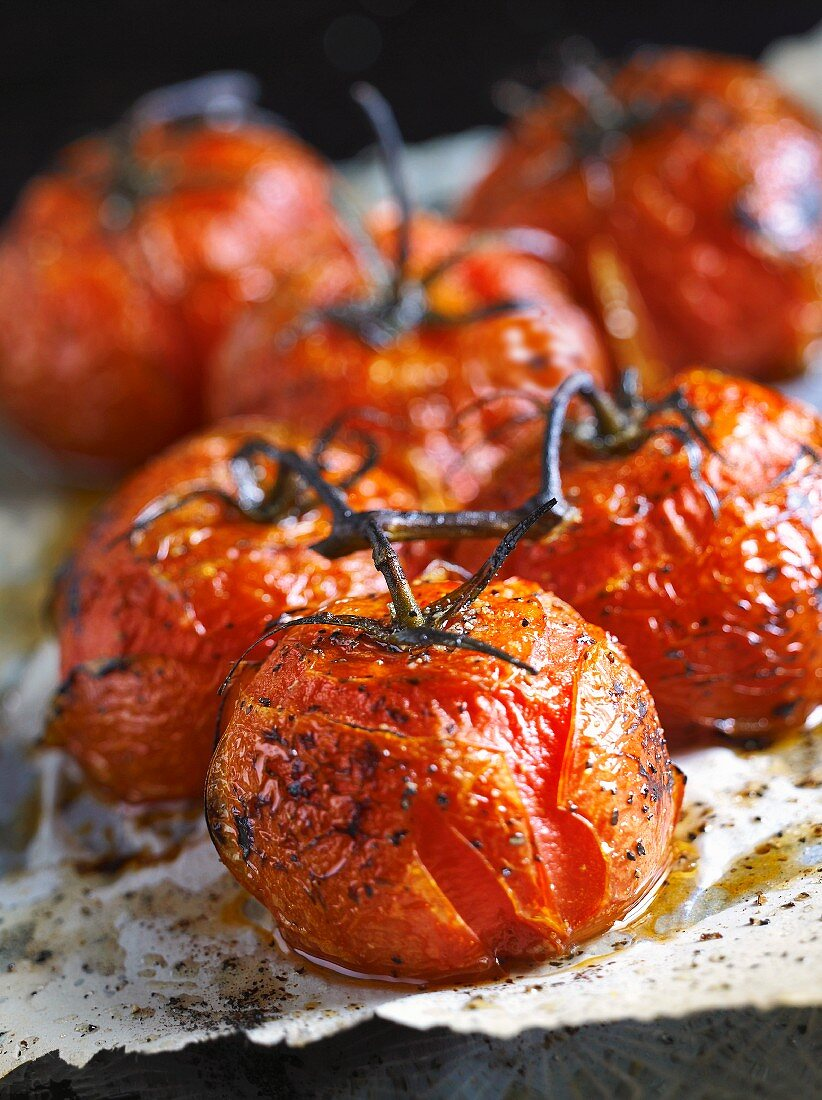 Roast tomatoes on a baking tray (close-up)