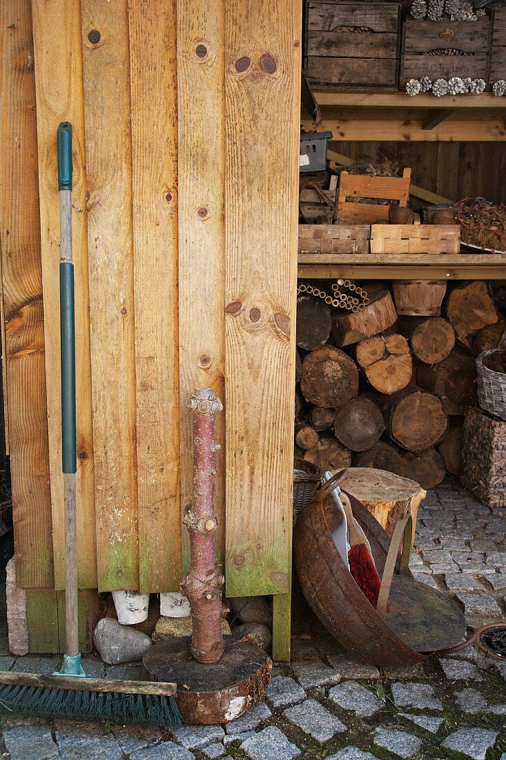 An old broom leaning against a wooden wall in front of a wood shed with crates on a shelf above