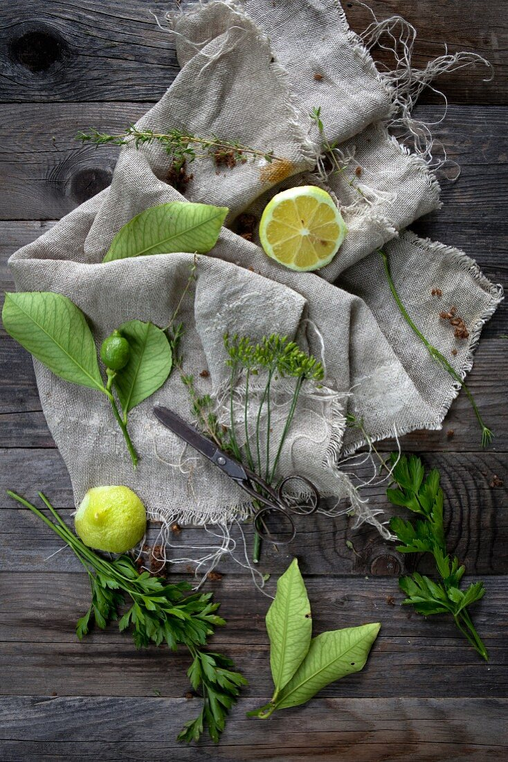 An arrangement of lemons and herbs on a linen cloth on a wooden table