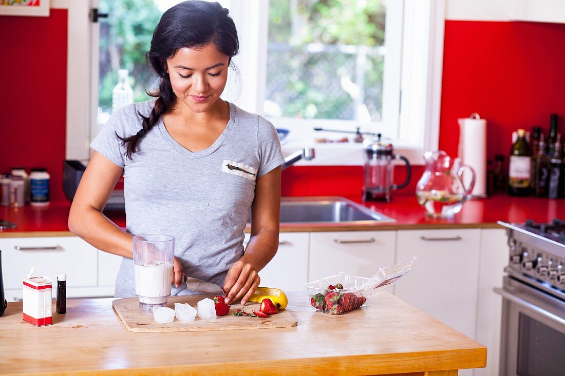A young woman slicing strawberries in a kitchen