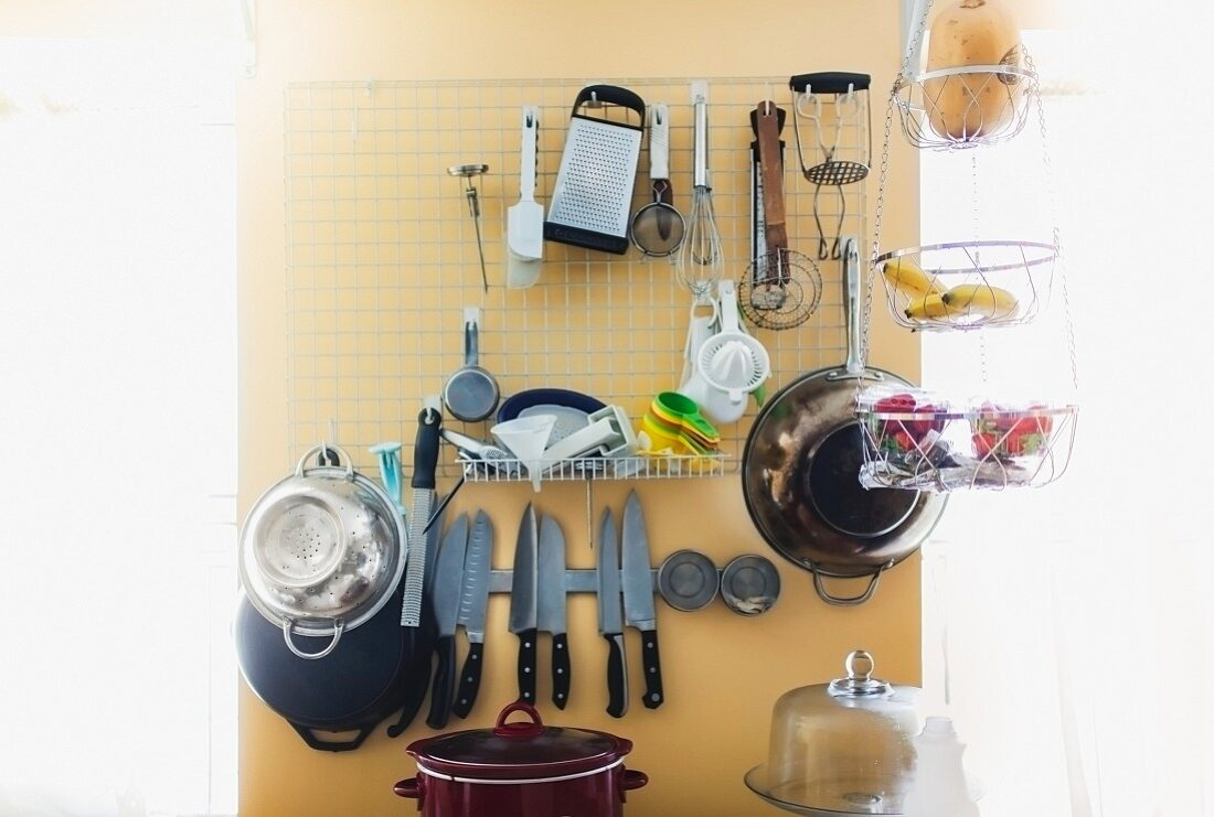Various kitchen utensils stored on a wall