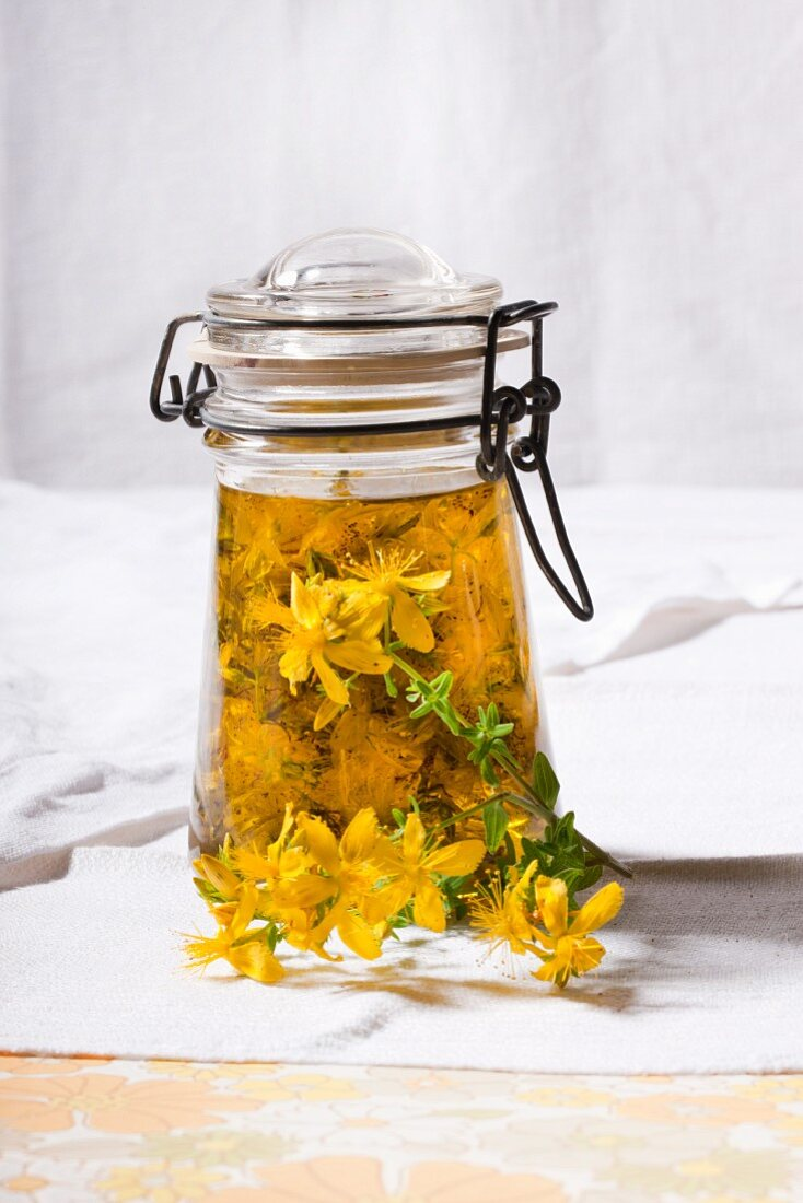 A jar of St John's Wort flowers in olive oil for making red oil