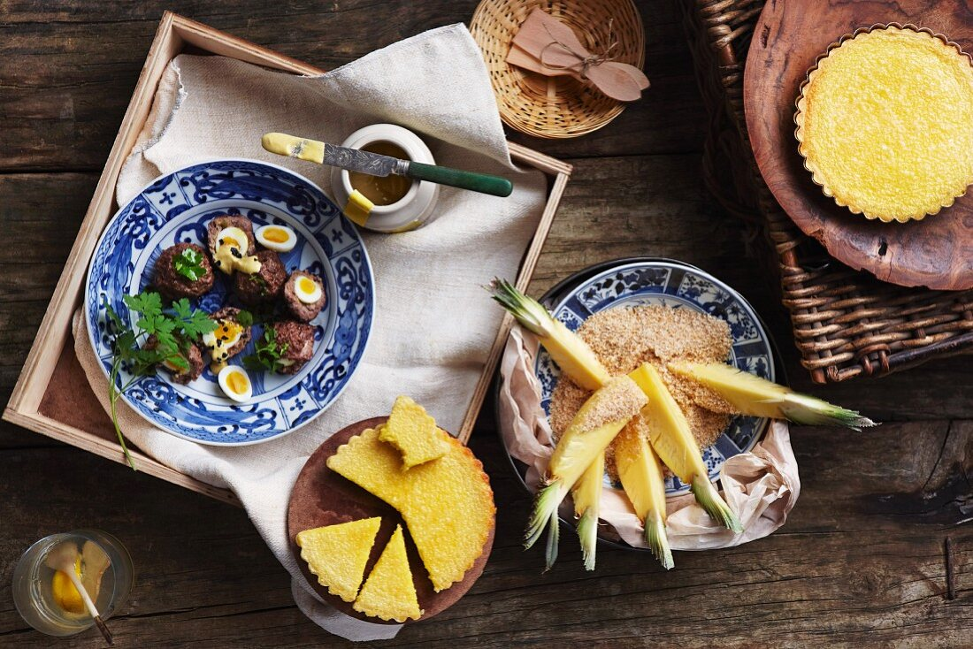 Scotch eggs, chocolate and coconut tartlets, and pineapple wedges with coconut
