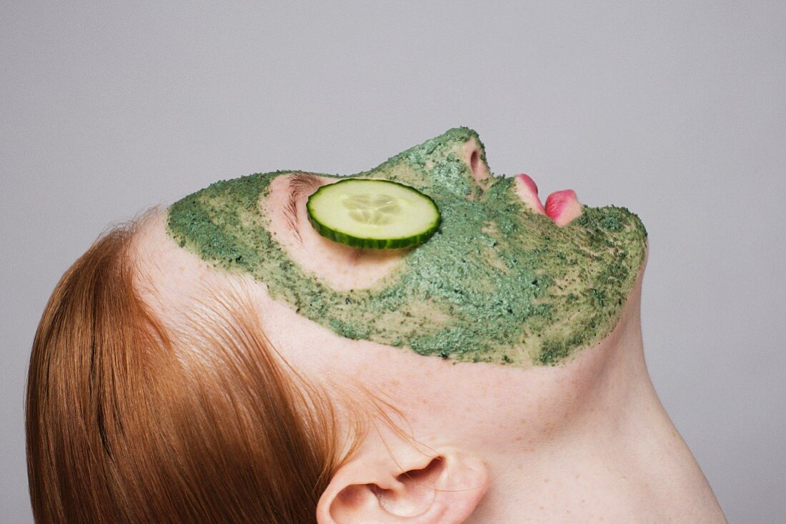 A young woman wearing a green face mask with slices of cucumber on her eyes