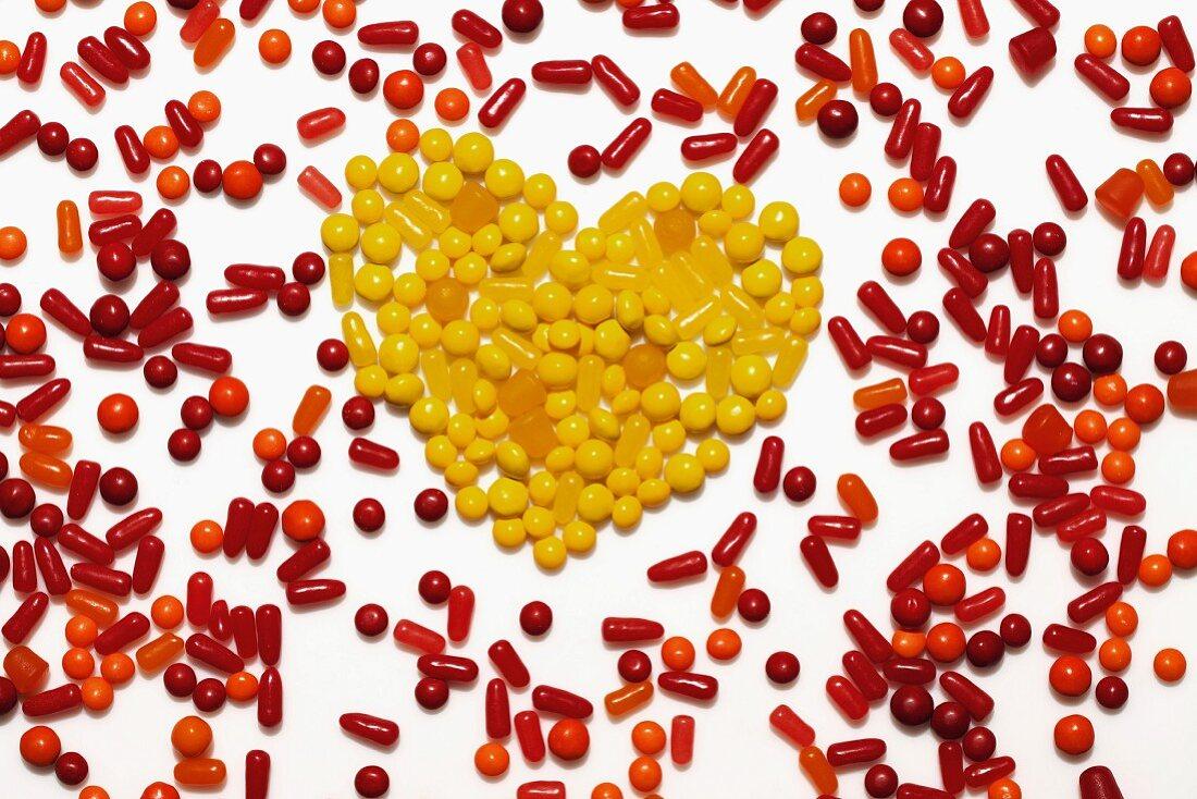Rot-orange Bonbons, in der Mitte Herz aus gelben Bonbons geformt