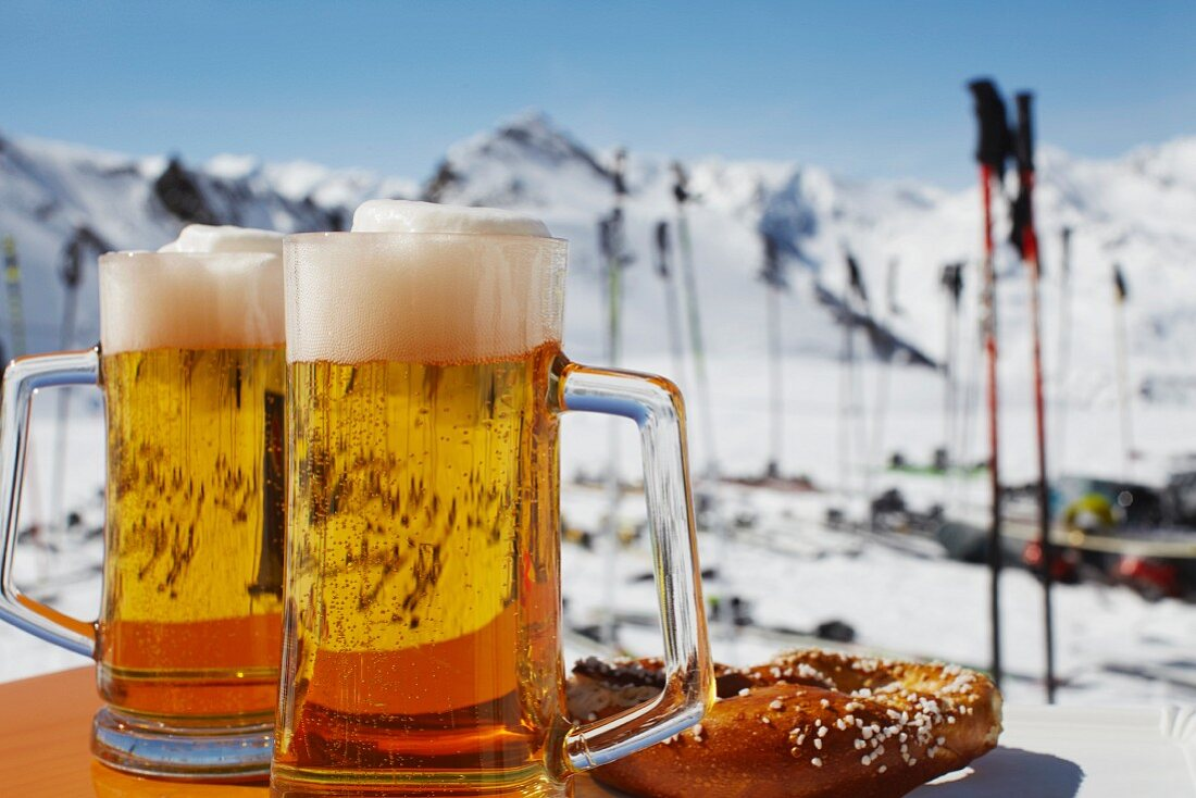 Two tankards of beer and a pretzel with a view of a ski run, Austria