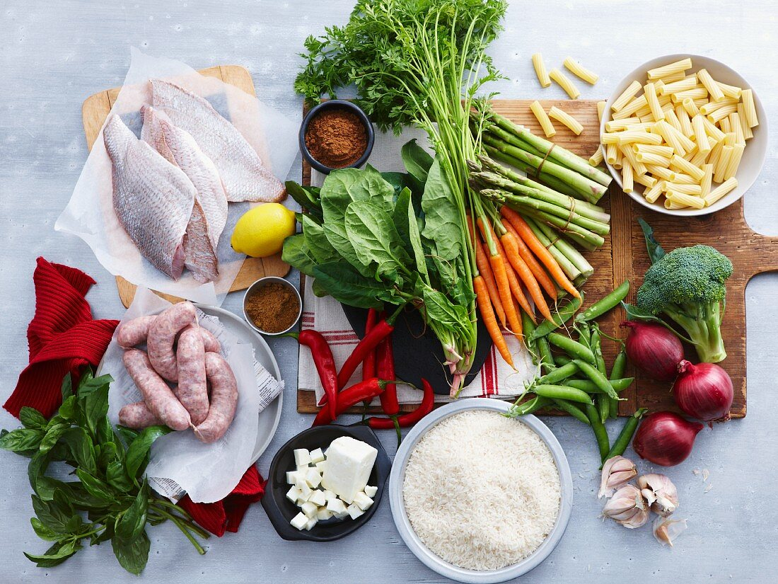 A overhead view of fish, sausage, feta and a selection of fresh, organic herbs and vegetables