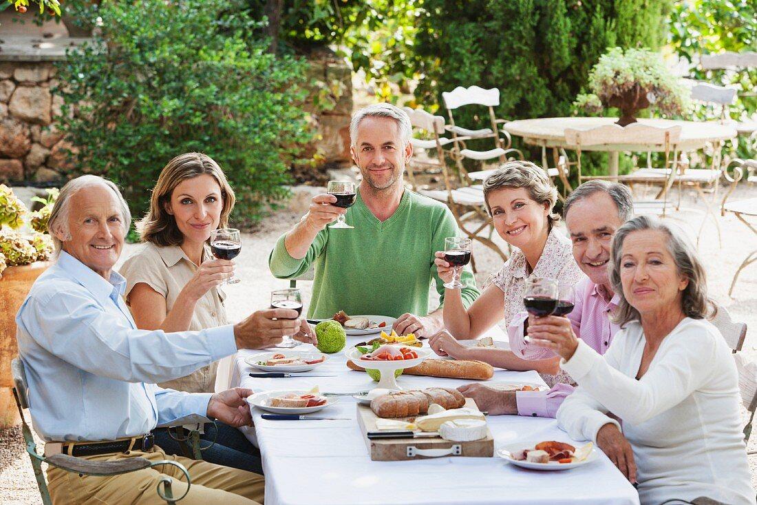 Drei Paare mittleren Alters im Garten bei Essen und Rotwein