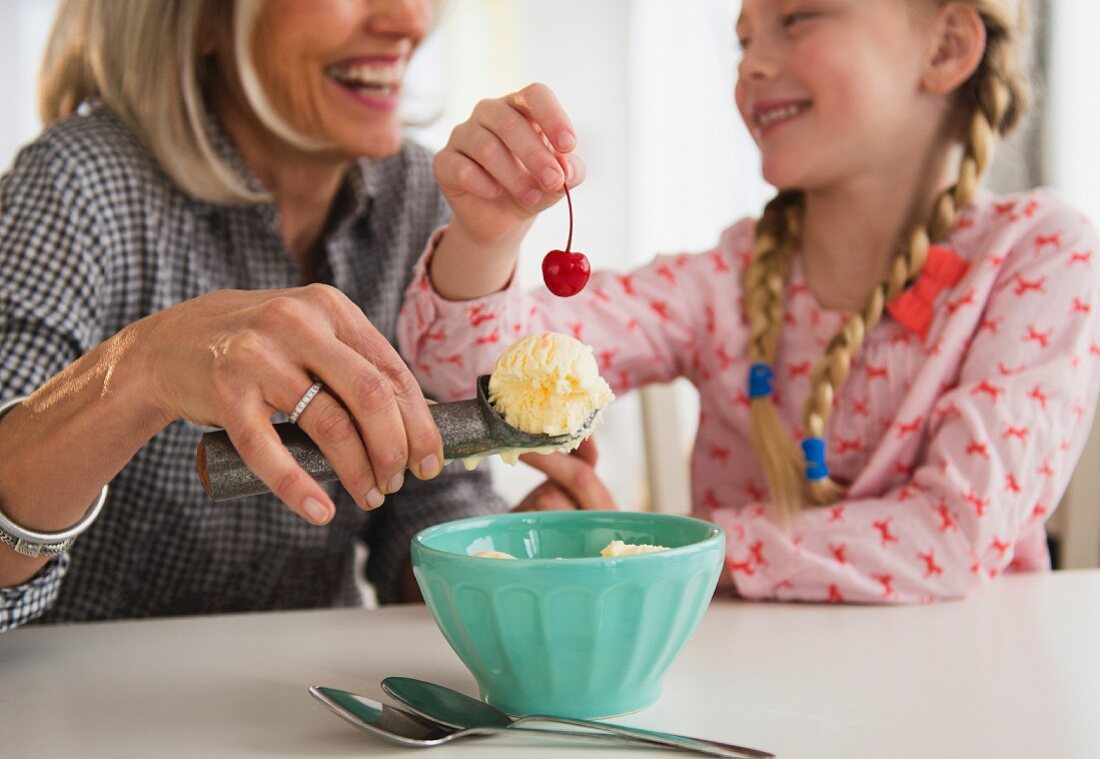 A grandma and her granddaughter making an ice cream dessert