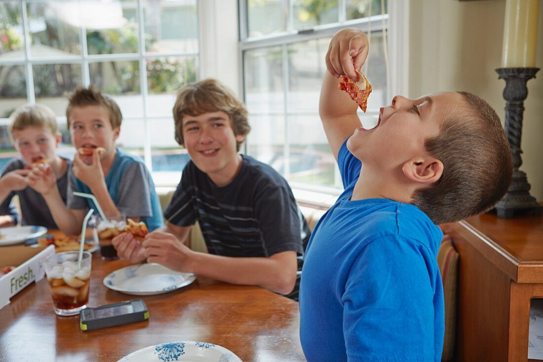 Boys eating pizza in a kitchen