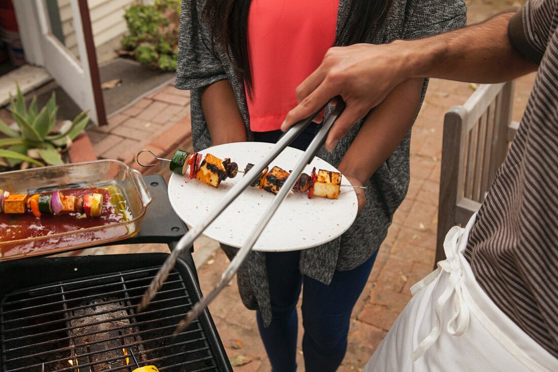 A man at a barbecue placing a vegetable skewer on a woman's plate using tongs