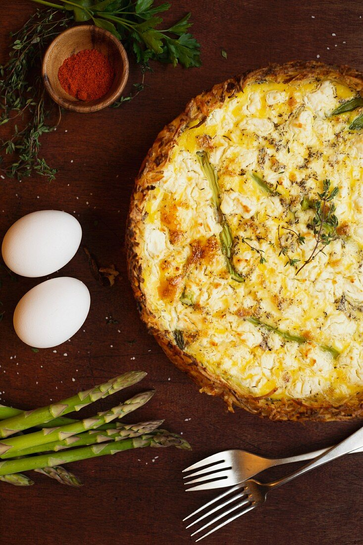 Quiche made with eggs, asparagus, pepper and thyme next to ingredients and forks