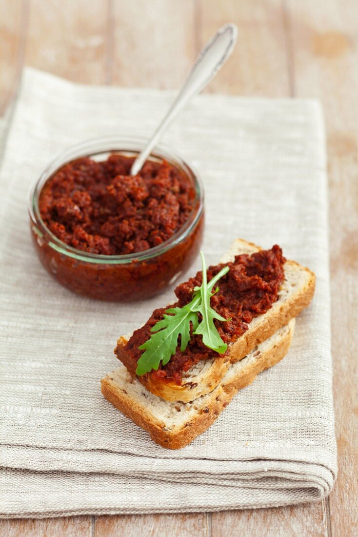 Dried tomato pesto on slice of white bread and in a jar