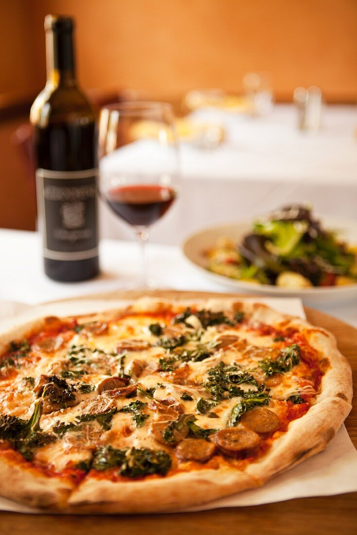 A pizza topped with wild boar sausage, braised green kale and smoked mozzarella cheese served with with wine and a salad