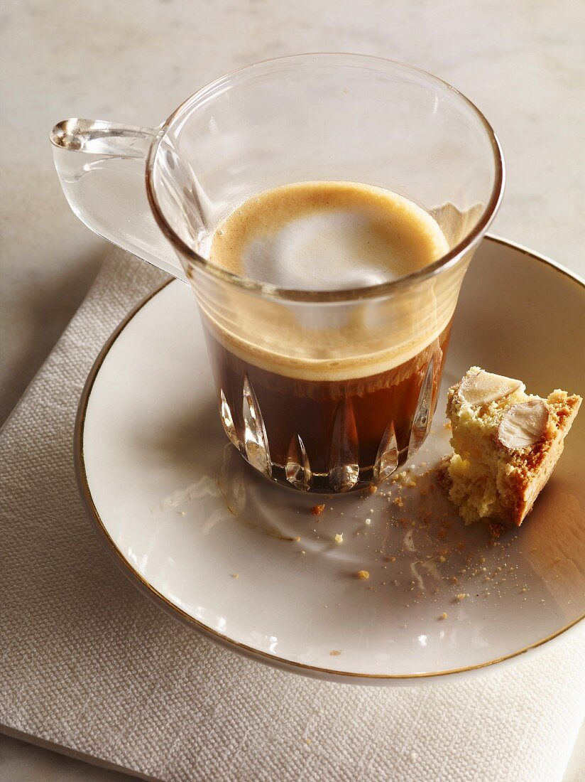 A macchiato in a glass cup on a saucer with biscotti