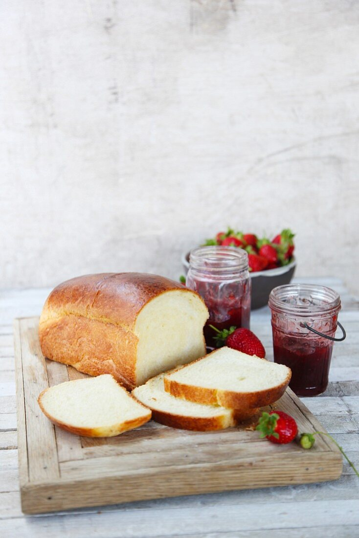Sliced white bread with strawberry jam and fresh strawberries