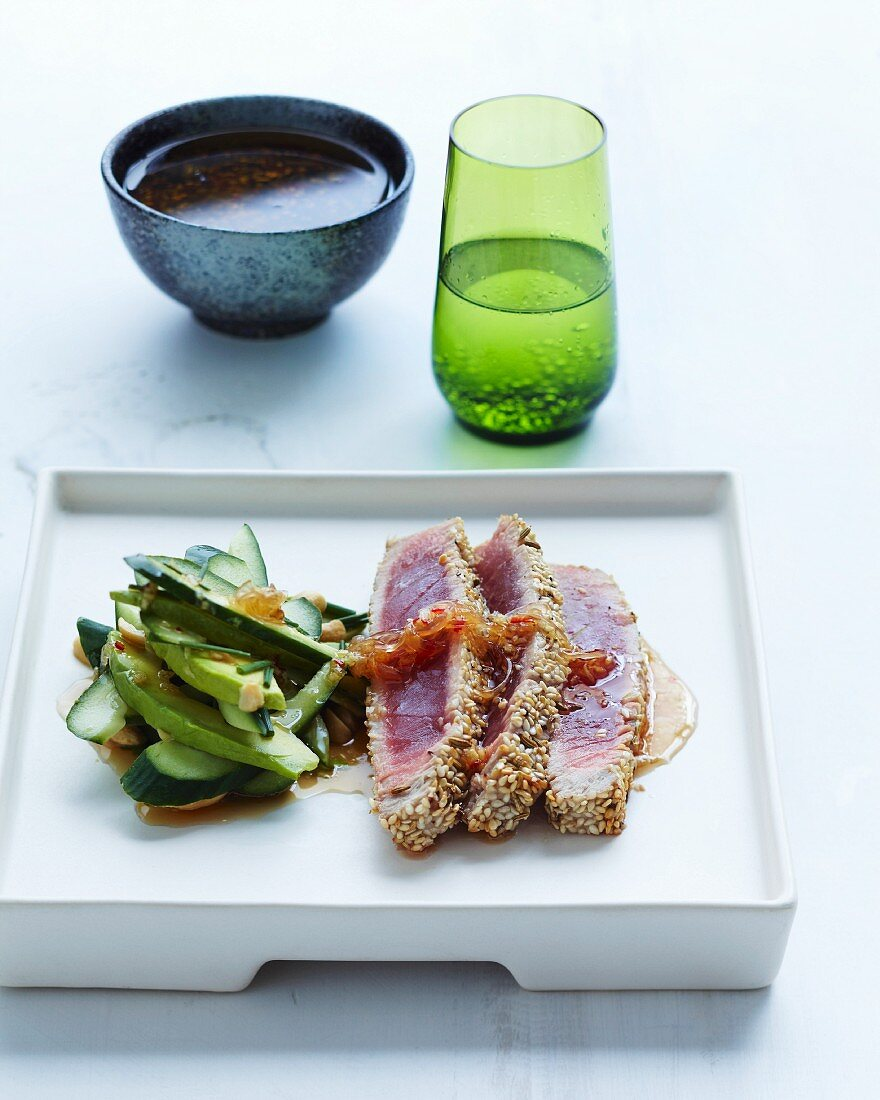 Pink tuna fish fillet with a sesame seed crust served with an avocado and cucumber salad